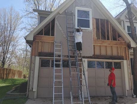 siding company in overland park ks installing new siding on a large house